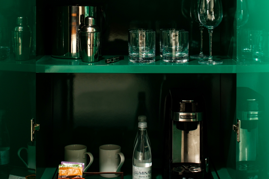 Multiple Bottles on Three Green shelves of Wet Bar in Hotel