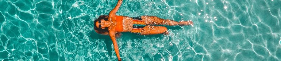 Aerial shot of woman floating on back in pool water in orange bikini